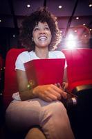 lachende jonge vrouw kijken naar een film foto