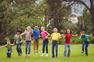 schattige leerlingen juichen op het gras buiten foto