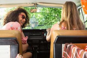 vrienden glimlachen tijdens het rijden in een busje