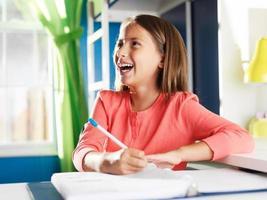 gelukkig meisje met thuiswerk in de kamer foto