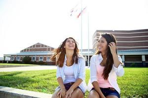 Aziatische vrouwelijke tieners bij de ingang van de middelbare school foto