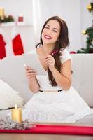 brunette liggend op de bank haar kerst lijst schrijven