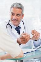 glimlachende arts die aan zijn patiënt luistert foto