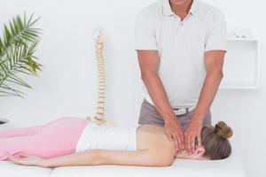 fysiotherapeut die nekmassage doet aan zijn patiënt foto