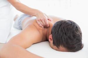 fysiotherapeut die schoudermassage doet aan haar patiënt foto