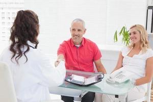 glimlachende patiënt die een arts raadpleegt foto