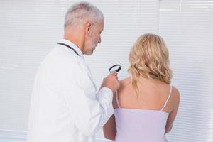 arts die patiënt met vergrootglas onderzoekt foto