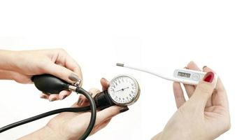 elektronische thermometer en bloeddruk in handen van vrouwen foto