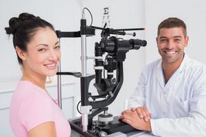gelukkig opticien en vrouwelijke patiënt met spleetlamp foto