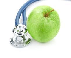 medische stethoscoop en appel die op wit wordt geïsoleerd foto
