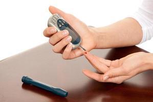 een diabetespatiënt die een kleine bloedtest gebruikt om glucose te meten foto