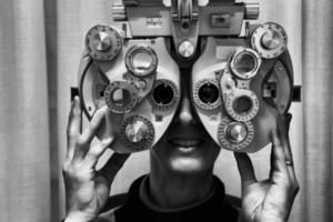 oogarts controleert het gezichtsvermogen van een patiënt foto