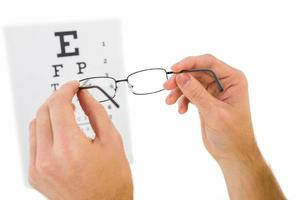 bril omhoog gehouden om oogtest te lezen foto