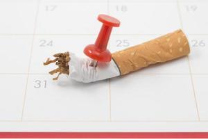 een kalender met een sigaretten duim vastgeplakt op de 31ste dag foto