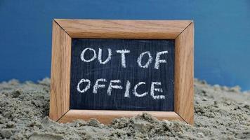 klein schoolbord in een frame met out of office op foto
