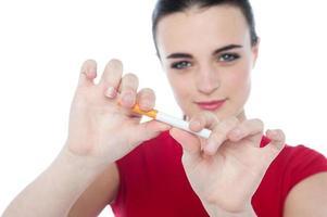 jonge vrouw probeert sigaret te breken foto