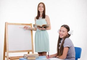 de leraar legt onderwerp van les bij bord uit foto