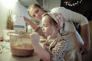 moeder die haar dochter in de keuken bijles geeft foto