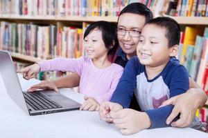 vrolijke studenten met leraar in de bibliotheek foto