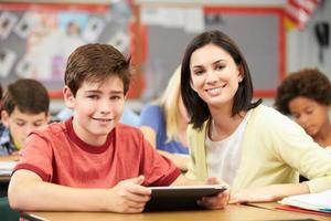 leerlingen in de klas met behulp van digitale tablet met leraar foto