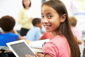 jong meisje in de klas met behulp van een digitale tablet foto
