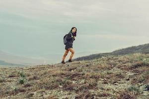 wandelaar vrouw klimmen in de bergen foto
