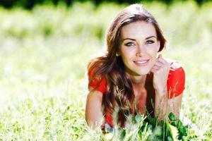 jonge vrouw in rode jurk liggend op gras foto