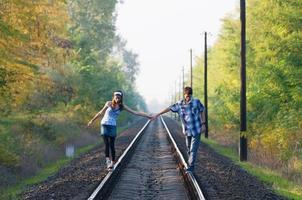 tiener meisje en jongen lopen op rails foto