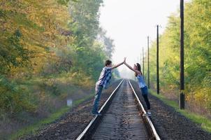 tiener meisje en jongen poseren op rails foto