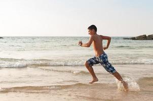 tienerjongen loopt langs het strand foto
