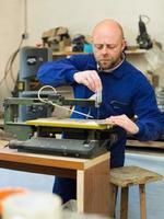 man aan het werk op een machine op hout workshop foto