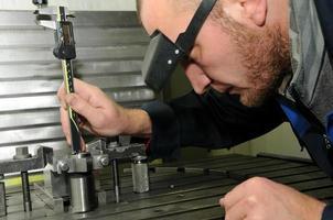 werknemer met behulp van een schuifmaat om meting te controleren