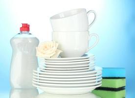 lege schone borden en kopjes met afwasmiddel en sponzen foto