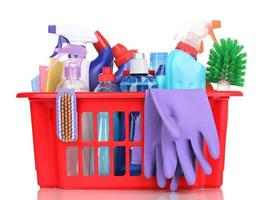 schoonmaak items in plastic mand op wit wordt geïsoleerd foto