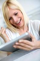positieve uitdrukking voor een blonde vrouw die digitale tablet gebruikt foto