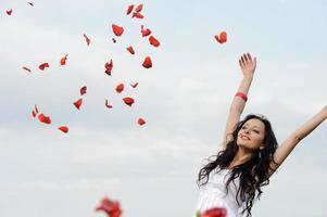 jonge vrouw gooit een rode klaproos bloemblaadjes over haar hoofd