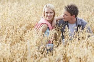 mooie jonge vrouw wegkijken zitten met vriendje in veld foto