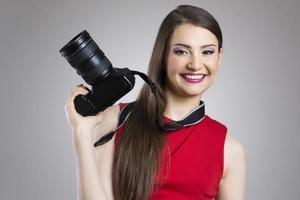 lachende jonge vrouw met fotocamera