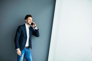 jonge man met mobiele telefoon bij de muur foto