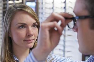 opticien die cliënt adviseert over de keuze van een bril