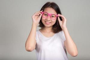 portret van Aziatisch tienermeisje dat en roze oogglazen glimlacht draagt foto