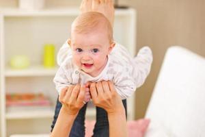 baby spelen met moeder thuis foto