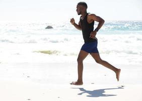 jonge man loopt werken op het strand