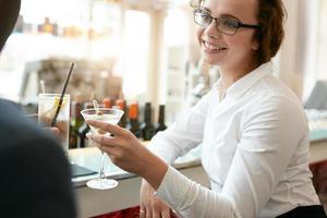 zakenvrouw roosteren drankje met collega in café foto