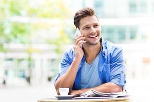 jonge man met behulp van mobiele telefoon buitenshuis foto