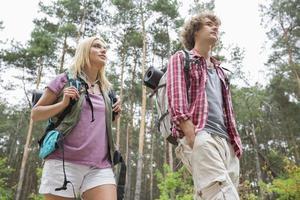 lage hoekmening van wandelend paar dat weg in bos kijkt foto