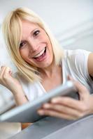 gelukkig blonde vrouw websurfen op tablet thuis foto