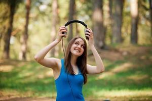 mooie jonge vrouw met een koptelefoon buitenshuis foto
