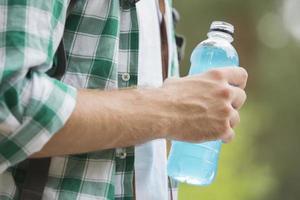 buik van man met energiedrank buitenshuis foto