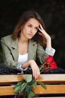 droevige jonge vrouw met rode rozen foto